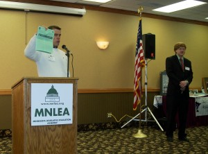Rep. Mark Buesgens holds up the LEA 2012 report on the legislature. LEA President John Augustine standing to his left.